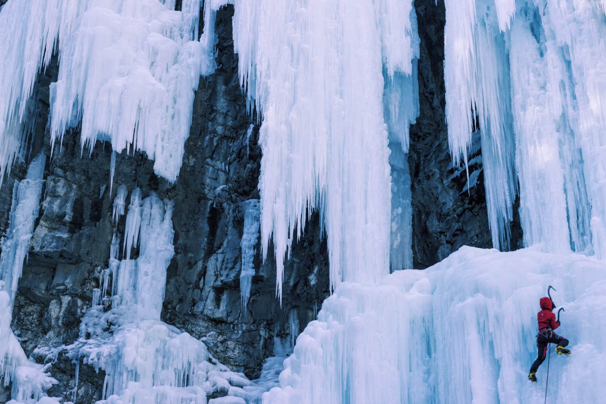 An ice climber ascending a frozen waterfall.